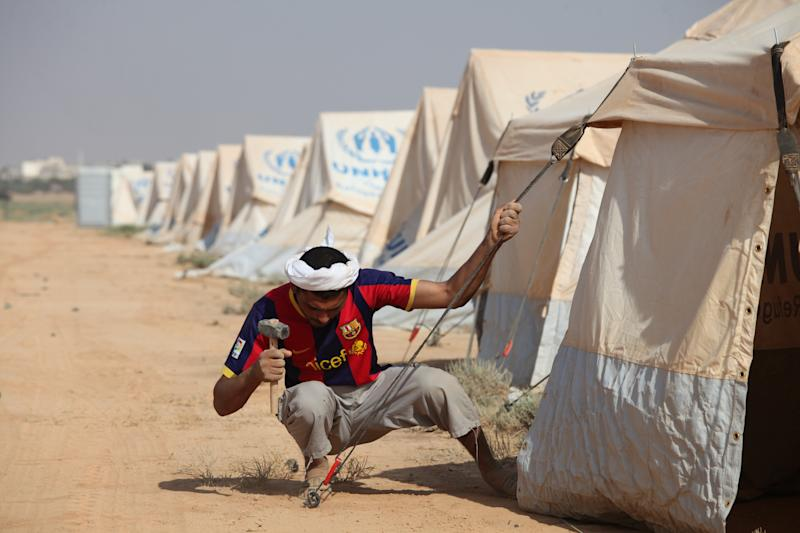 A Jordanian works preparing the first Jordanian tent camp for Syrian refugees fleeing violence in their country in Zataari, Jordan, near the Syrian border, Sunday, July 29, 2012. Authorities had been reluctant to set up the camps, but with at least 142,000 Syrians seeking refuge and their numbers growing daily by up to 2,000, Jordanian Foreign Minister Nasser Judeh said Sunday that Jordan had no other choice. (AP Photo/Mohammad Hannon)