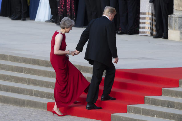 <p>British Prime Minister Theresa May takes the hand of President Donald Trump as they walk up red-carpeted steps to enter Blenheim Palace for a black tie dinner in Blenheim, England, Thursday, July 12, 2018. (Photo: Will Oliver/Photo via AP) </p>