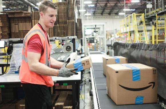 A warehouse worker placing an Amazon package on a conveyor belt.