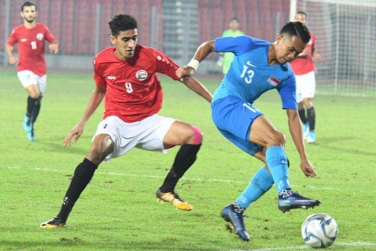 Singapore winger Hafiz Nor (right) tussles for the ball with Yemen's Omar Abdullah Al-Dahi during their 2022 World Cup qualifier in Bahrain. (PHOTO: Football Association of Singapore/Courtesy of Bahrain FA)