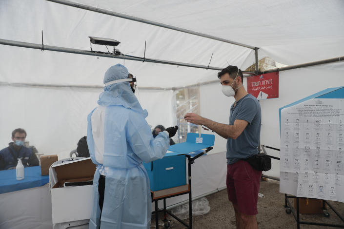 A man votes for Israel's parliamentary election at a special polling station for people who are in quarantine for coronavirus in Jerusalem, Tuesday, March 23, 2021. (AP Photo/Maya Alleruzzo)
