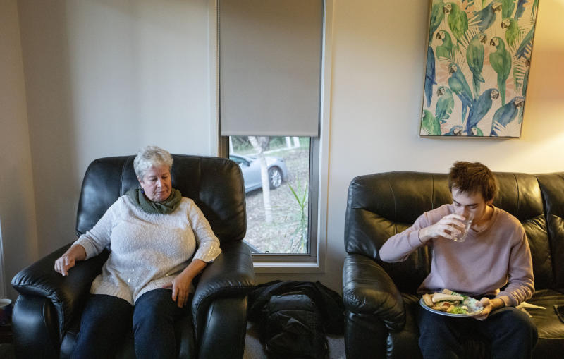 Sam Ware, 22, eats as his mother, Deb Ware, sits by, upon letting him return to her home for the first time since he last overdosed, in Fountaindale, Central Coast, Australia, Friday, July 19, 2019. Deb lets Sam inside, into the warmth of the living room. He sits on the couch where he overdosed three weeks earlier and wolfs down a sandwich, and toast, and cereal, and cookies. Deb sinks into her armchair, looking broken. (AP Photo/David Goldman)