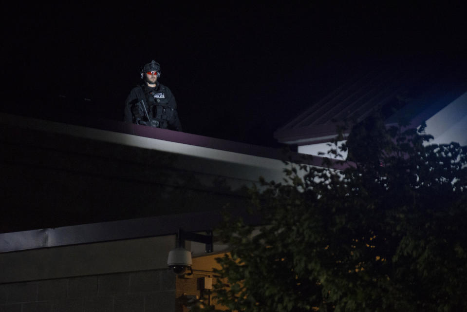 CORRECTS DAY TO FRIDAY - A Portland police officer watches from the roof of the Multnomah County Sheriff's Office while about 200 people protest on Friday, Aug. 7, 2020 in Portland, Ore. Police say demonstrators threw or launched items including rocks, frozen or hard-boiled eggs and commercial-grade fireworks toward officers early Saturday. (AP Photo/Nathan Howard)