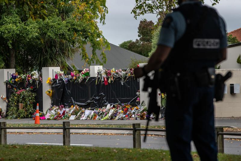 Flowers lie by the wall of Al Noor mosque as an armed policeman guards nearby on March 21, 2019 in the wake of the attacks. Source: Getty