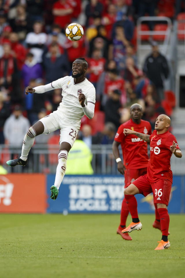 Toronto FC defender Auro Jr. (96) watches as Colorado Rapids forward Kei Kamara (23) hits a header in the first half of MLS soccer action at BMO Field in Toronto, Sunday, Sept. 15 2019. (Cole Burston/The Canadian Press via AP)