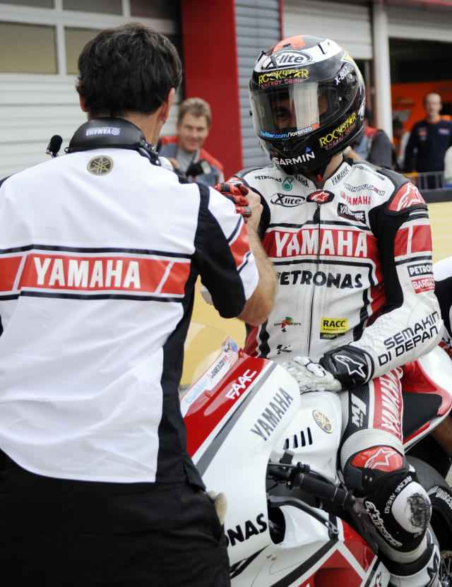 Jorge Lorenzo of Italy is congratulated by a teammate during the Moto GP class qualifying practice session of the motorcycle Grand Prix of Japan at Twin Ring Motegi circuit in Motegi on October 1, 2011. Australian Moto GP world championship leader Casey Stoner will start on pole at the Grand Prix of Japan after recording the fastest time in qualifying on October 1.AFP PHOTO / TOSHIFUMI KITAMURA (Photo credit should read TOSHIFUMI KITAMURA/AFP/Getty Images)