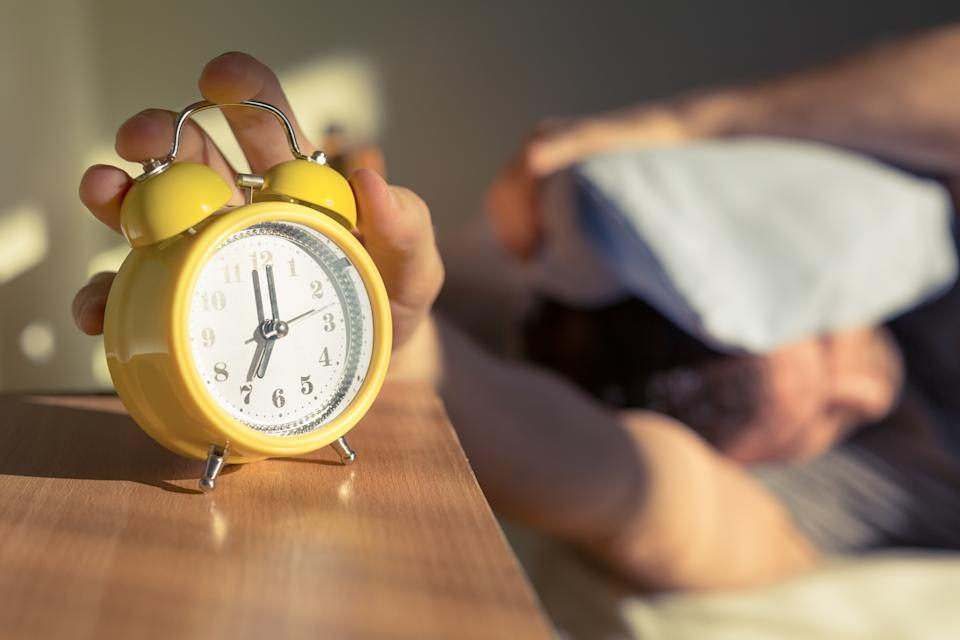 Sleeping man disturbed by alarm clock early in the morning.