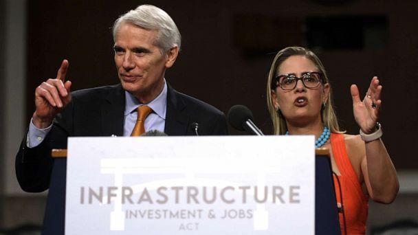 PHOTO: *** BESTPIX *** WASHINGTON, DC - JULY 28:  U.S. Sen. Rob Portman (R-OH) (L) and Sen. Kyrsten Sinema (D-AZ) (R) answer questions from members of the press during a news conference after a procedural vote for the bipartisan infrastructure framework. (Alex Wong/Getty Images)