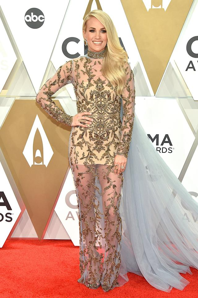 """<a href=""""https://people.com/style/cmas-2019-carrie-underwood-red-carpet-look-outfit-changes/"""" target=""""_blank"""">wears her first of 12 looks</a> — a show-stopping, sequin-covered Elie Madi gown featuring a sheer skirt and a tulle cape and train, accessorized with Jimmy Choo heels, Jared Lehr earrings and rings from Loree Rodkin and Maxior."""