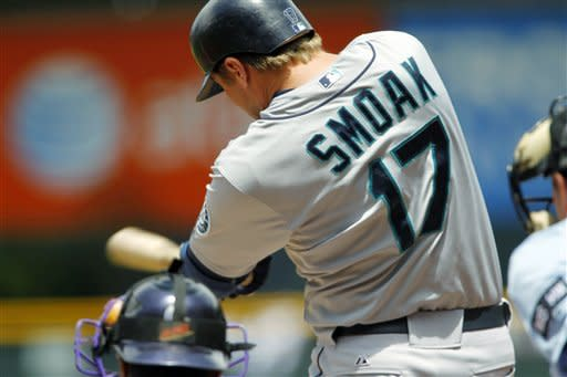 Seattle Mariners' Justin Smoak connects for an RBI-single against Colorado Rockies starting pitcher Jeremy Guthrie in the first inning of an interleague baseball game in Denver on Sunday, May 20, 2012. (AP Photo/David Zalubowski)