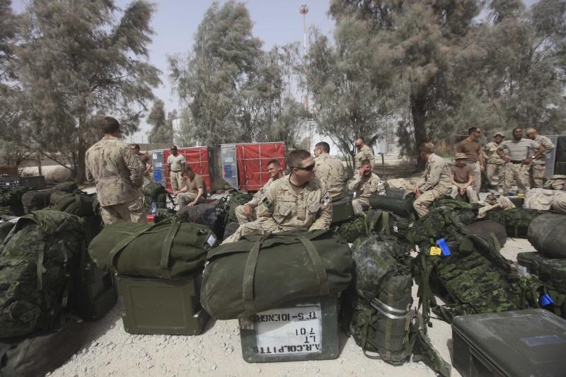 FILE -- In this Sunday, July 17, 2011 file photo Canadians soldiers wait with their baggage at Kandahar airbase in Afghanistan. Canada withdrew 2,850 combat forces from Afghanistan this summer; (AP Photo/Rafiq Maqbool/file)