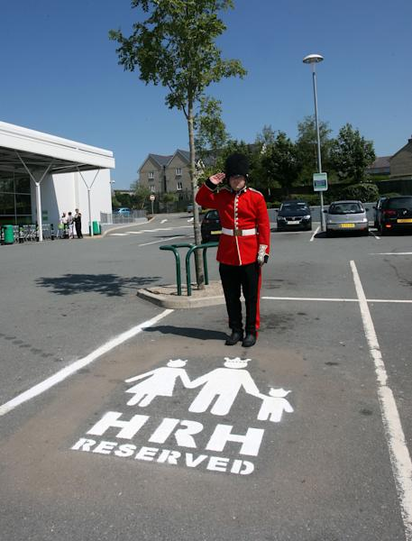 LLANGEFNI, WALES - JULY 11: In this handout image supplied by Asda Llangefni on July 11, 2013, a man dressed as a member of the queen's guard poses beside a parking space reserved for a prospective prince or princess, as the Duke and Duchess of Cambridge prepare for the birth of their first child. The supermarket, on the island of Anglesey is situated near to the home that the Duke and Duchess of Cambridge share. (Photo by Richard Birch/Asda via Getty Images)