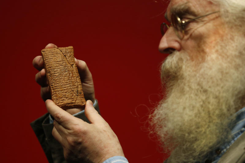 Irving Finkel, curator in charge of cuneiform clay tablets at the British Museum, poses with the 4000 year old clay tablet containing the story of the Ark and the flood during the launch of his book 'The Ark Before Noah' at the British Museum in London, Friday Jan. 24, 2014. The book tells how he decoded the story of the Flood and offers a new understanding of the Old Testament's central narratives and how the flood story entered into it. (AP Photo/Sang Tan)