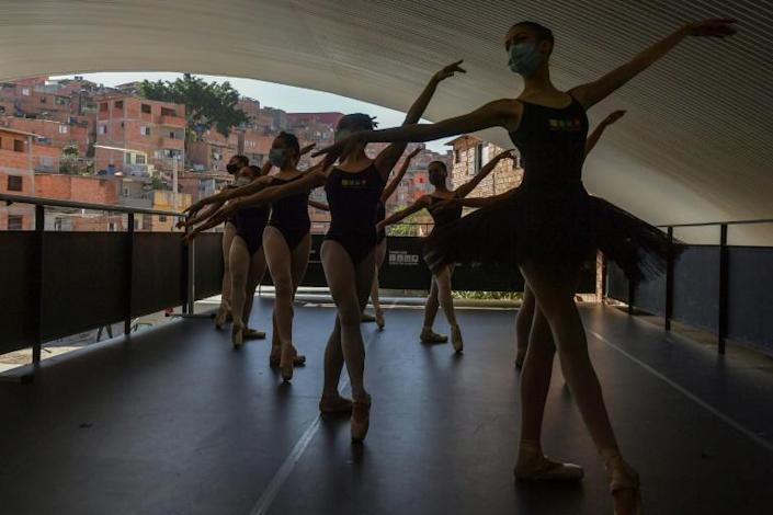 Wearing face masks, the dancers practice for four hours a day, five days a week