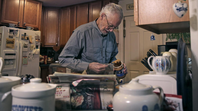 In this Nov. 22, 2019, photo, Charles Flagg, who is stricken with Alzheimer's disease, makes a peanut butter sandwich for lunch at his family home in Jamestown, R.I. Flagg is participating in a study on the drug Aducanumab. New results were released on the experimental medicine whose maker claims it can slow the decline of Alzheimer's disease, the most common form of dementia. (AP Photo/Charles Krupa)