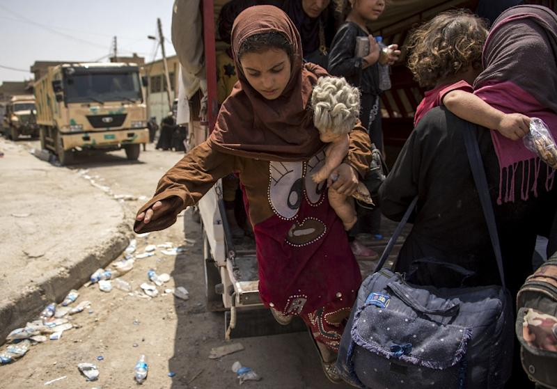 An Iraqi girl, who fled fighting between government forces and jihadists in the Old City of Mosul, holds a doll in her arm as she disembarks from a vehicle in the city's western industrial district on July 8, 2017 (AFP Photo/Fadel SENNA)