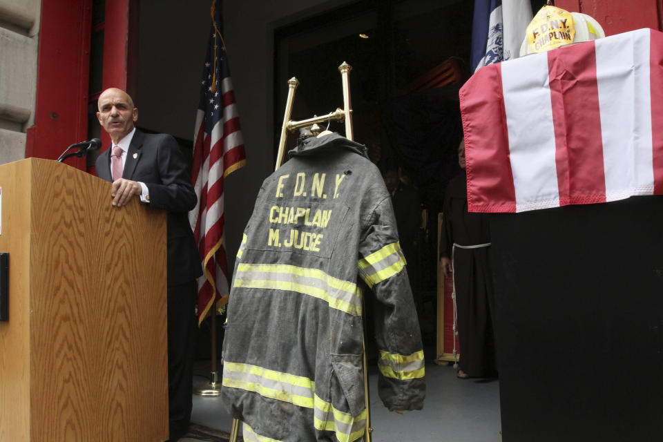 FILE - In this Sunday Sept. 11, 2011 file photo, the bunker coat and helmet worn by FDNY Chaplain Mychal Judge are displayed as City of New York Fire Commissioner Salvatore J. Cassano speaks at the New York City Fire Museum in New York during a memorial ceremony for the 343 members of the FDNY who lost their lives in the World Trade Center attacks. The bunker coat and helmet worn by Father Judge on Sept. 11, 2001, were dedicated to the museum during the service. (AP Photo/Tina Fineberg, File)