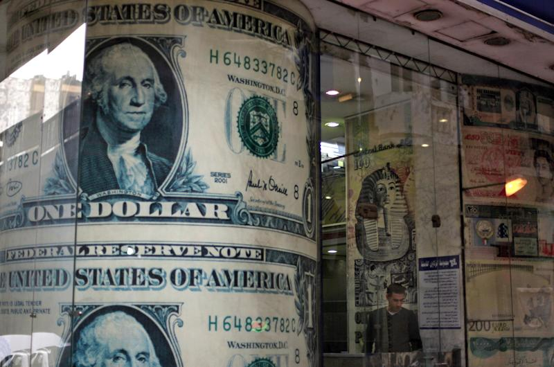 An Egyptian man stands next to a giant poster of U.S. dollars inside a currency exchange office in Cairo, Egypt, Tuesday, Dec. 25, 2012. As Egypt prepared to release official results from the constitutional referendum, its economy showed increasing signs of distress on Tuesday with worried residents hoarding dollars and fearing that continued political instability will lead to a fast devaluation of the local currency. The Central Bank of Egypt said Tuesday that the U.S. dollar was selling at 6.18 to the Egyptian pound, a spike from the rate of six pounds just two months ago. (AP Photo/Khalil Hamra)