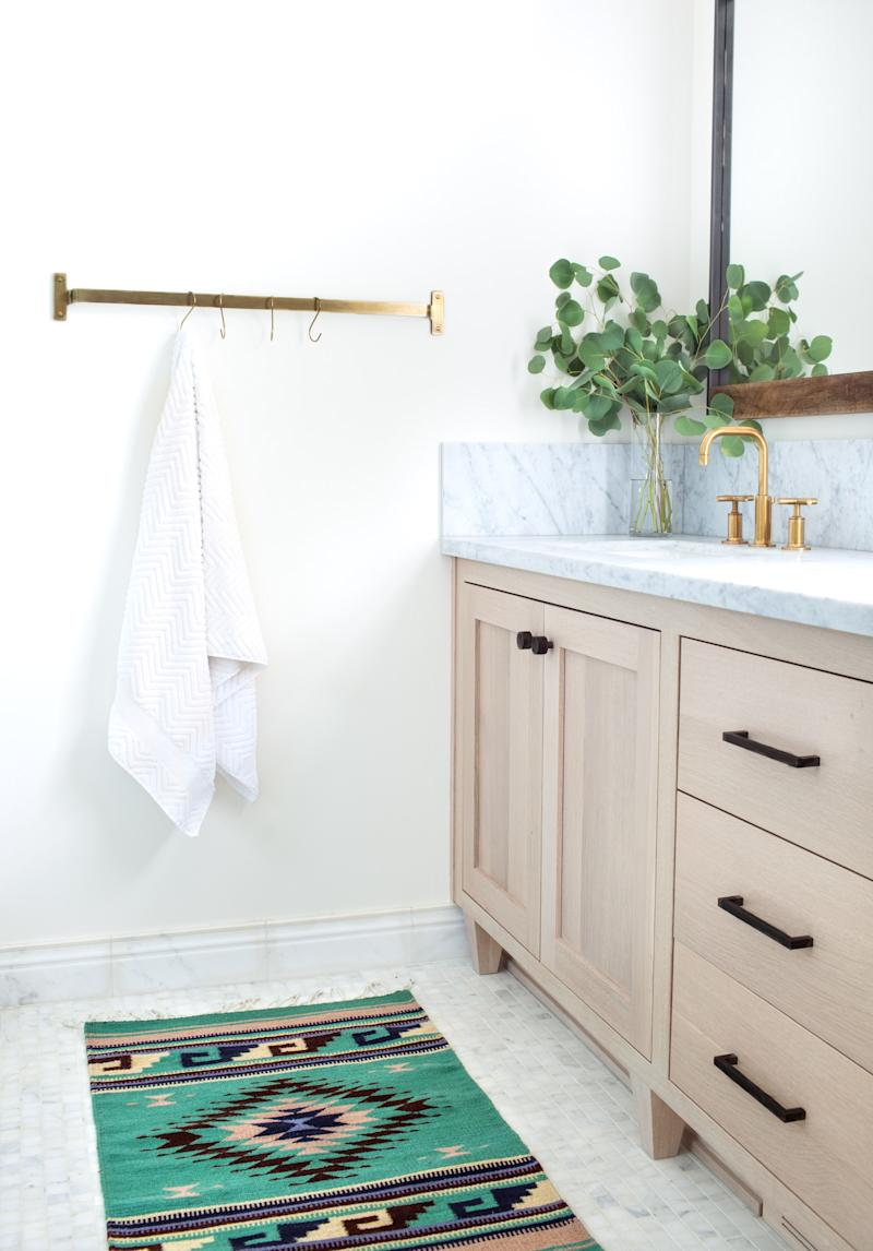 Design firm Townsend Interiors outfitted a standard brass towel bar with matching S-hooks.