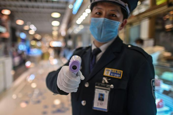 "A guard holds a thermal gun to check the body temperature of visitors at the entrance of a restaurant area in China. <span class=""copyright"">(Hector Retamal / AFP-Getty Images)</span>"