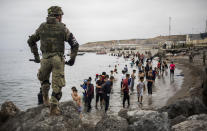 People mainly from Morocco stand on the shore as Spanish Army cordon off the area at the border of Morocco and Spain, at the Spanish enclave of Ceuta, on Tuesday, May 18, 2021. Ceuta, a Spanish city of 85,000 in northern Africa, faces a humanitarian crisis after thousands of Moroccans took advantage of relaxed border control in their country to swim or paddle in inflatable boats into European soil. Around 6,000 people had crossed by Tuesday morning since the first arrivals began in the early hours of Monday, including 1,500 who are presumed to be teenagers. (AP Photo/Javier Fergo)