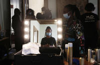 """An hairdresser is reflected in a mirror as she waits in the backstage at the """"We are Made in Italy - Black Lives Matter in Italian fashion Collection"""" event during the Milan's fashion week in Milan, Italy, Thursday, Sept. 17, 2020. (AP Photo/Antonio Calanni)"""