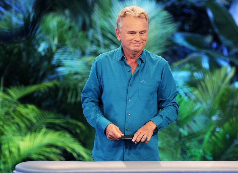 Pat Sajak stands at the Wheel of Fortune wheel wearing a blue button down shirt in front of a tropical background