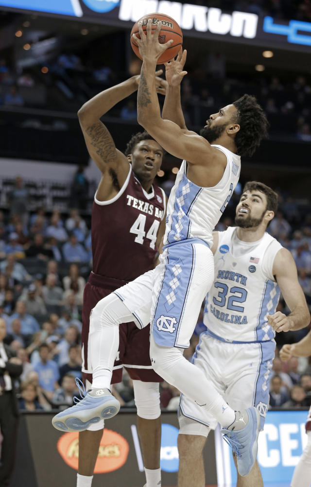 North Carolina's Joel Berry II, front, drives past Texas A&M's Robert Williams, back, during the first half of a second-round game in the NCAA men's college basketball tournament in Charlotte, N.C., Sunday, March 18, 2018. (AP Photo/Bob Leverone)