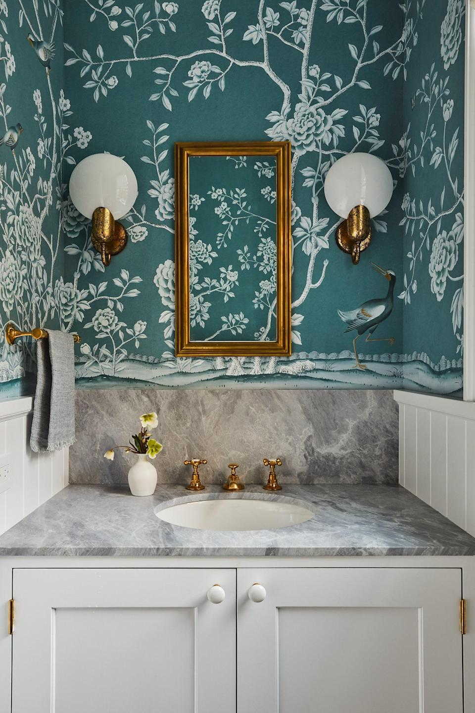 """""""I always feel like the powder room should be a little more fun,"""" says Kamel. Here, custom De Gournay wallpaper becomes a lively backdrop for Urban Electric Company sconces and an Ann-Morris mirror."""