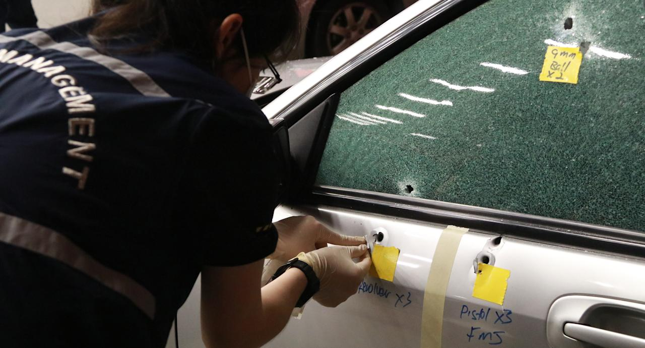 <p>Course participants during the Shooting Reconstruction Workshop mark bullet holes at the crime scene. <br /> Photo: Hannah Teoh/Yahoo News Singapore </p>