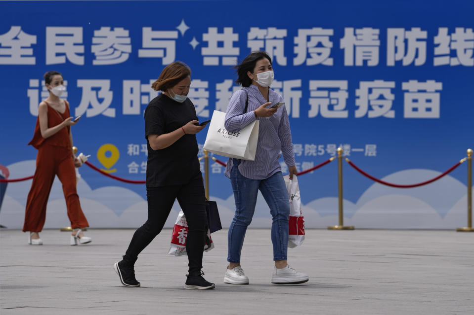 """Women wearing face masks to help curb the spread of the coronavirus walk by a billboard showing the words """"All people participate in building a line of defense against the epidemic, please get the vaccine in time"""" on display outside a shopping mall in Beijing, Monday, May 24, 2021. (AP Photo/Andy Wong)"""