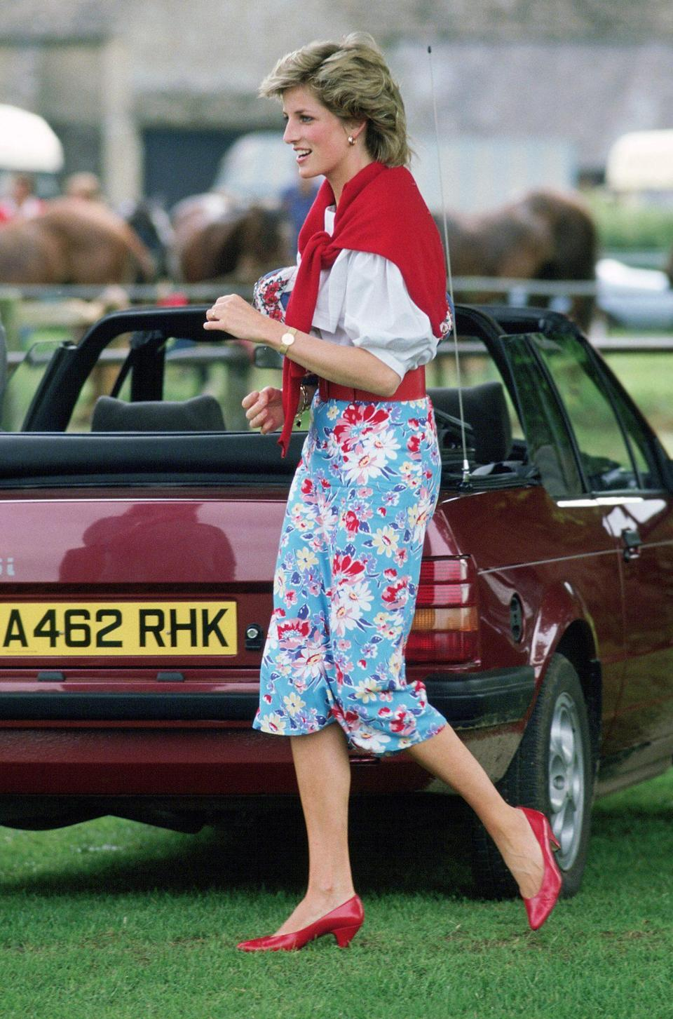 <p>Princess Diana had the perfect practical accessory at a polo game in 1985, casually tying a red sweater (which complemented her floral pants and matched her shoes) over her shoulders.</p>