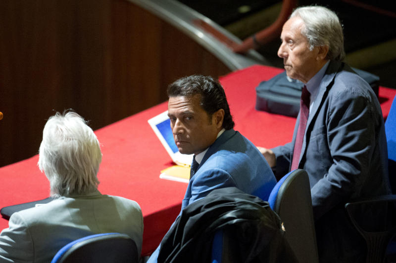 Captain Francesco Schettino, center, sits in the court room of the converted Teatro Moderno theater on the second day of his trial, in Grosseto, Italy, Tuesday, Sept. 24, 2013. The captain of the wrecked Costa Concordia is charged with manslaughter, causing the shipwreck and abandoning ship before the luxury cruise liner's 4,200 passengers and crew could be evacuated on Jan. 13, 2012 when the ship collided with a reef off the Tuscan island of Giglio, killing 32 people. Schettino blames his helmsman for botching a last-minute corrective maneuver that he contends could have prevented the massive cruise ship's collision with the reef. (AP Photo/Andrew Medichini)