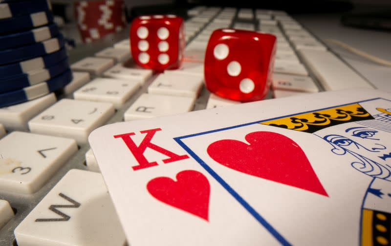 FILE PHOTO: Gambling dice, cards and chips are seen on the keyboard in this illustration picture