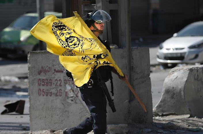 An Israeli policeman with a seized flag, bearing a portrait of late Palestinian leader Yasser Arafat, after clashes with Palestinians on September 18, 2015 near the West Bank city of Ramallah (AFP Photo/Thomas Coex)