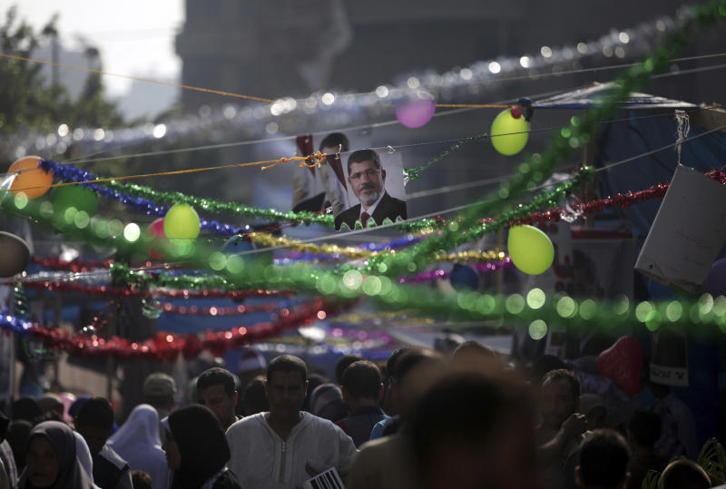 Supporters of Egypt's ousted President Mohammed Morsi celebrate the Eid al-Fitr holiday, marking the end of the Muslim holy fasting month of Ramadan that is traditionally celebrated with special cookies, presents and new clothes, outside Rabaah al-Adawiya mosque, where protesters have installed a camp and hold daily rallies at Nasr City in Cairo, Egypt, Thursday, Aug. 8, 2013. This year's holiday of Eid al-Fitr is overshadowed by the deep divisions in Egypt, with the interim government planning to celebrate the festival with outdoor prayers in town center squares and Morsi's supporters marking the holiday with their own protest gatherings, including the two major sit-ins by the Islamists in Cairo. (AP Photo/Khalil Hamra)