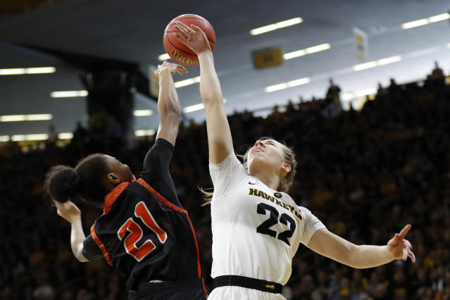 FILE - In this March 24, 2019, file photo, Mercer guard Shannon Titus blocks a shot by Iowa guard Kathleen Doyle, right, during a first-round game in the NCAA women's college basketball tournament in Iowa City, Iowa. Iowa has won six straight games and is on a 30-game home win streak, second-longest in the nation behind Baylor's 49-game streak. (AP Photo/Charlie Neibergall, File)