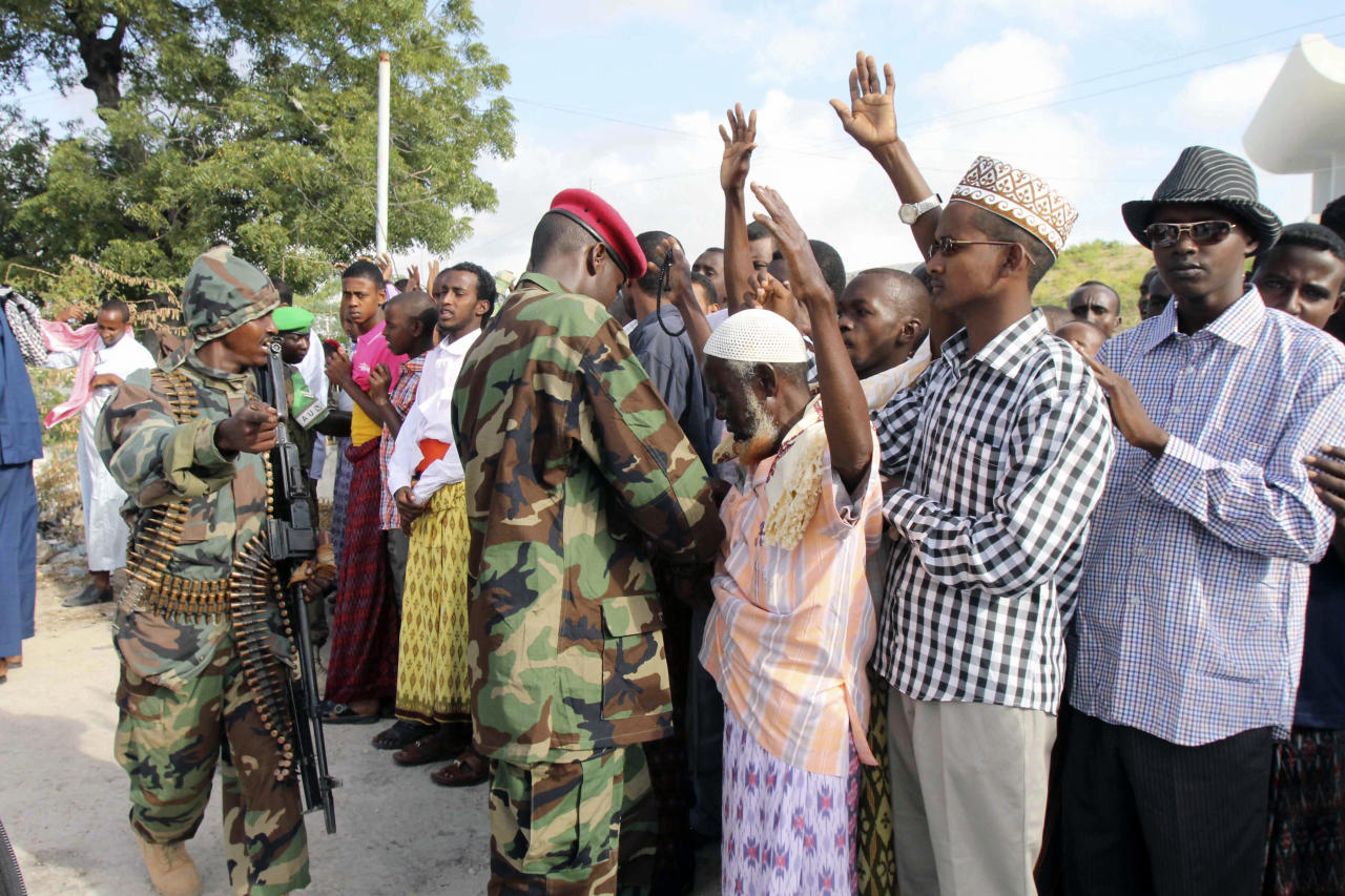 Somali government soldiers check people entering Isbahaysi Mosque in Mogadishu,Somalia during Eid al Fitr prayers Sunday Aug, 19, 2012. (AP Photo/Farah Abdi Warsameh)