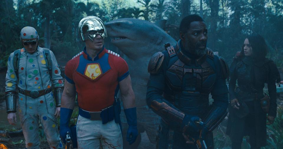 """Peacemaker (John Cena, front left) traverses the jungle with teammates Polka-Dot Man (David Dastmalchian), King Shark (voiced by Sylvester Stallone), Bloodsport (Idris Elba) and Ratcatcher 2 (Daniela Melchior) in """"The Suicide Squad."""""""