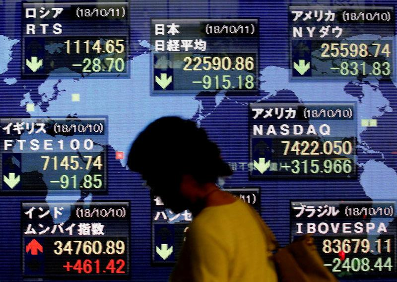 FILE PHOTO: A woman walks past an electronic board showing the stock market indices of various countries outside a brokerage in Tokyo, Japan, October 11, 2018. REUTERS/Kim Kyung-Hoon/File Photo