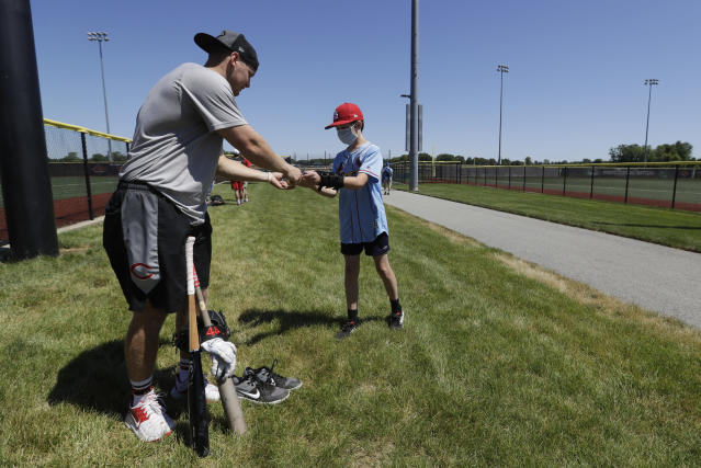 Cincinnati Reds' Josh VanMeter signs an autograph for Sam Berry following a workout at Grand Park, Friday, June 12, 2020, in Westfield, Ind. Proceeds from the event will go to Reviving Baseball in the Inner City of Indianapolis. (AP Photo/Darron Cummings)