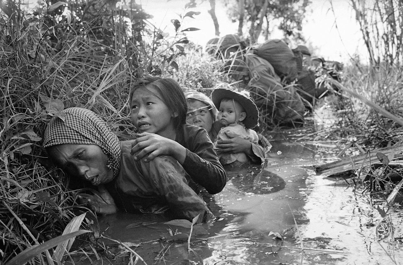 FILE - In this Jan. 1, 1966 file photo taken by Associated Press photographer Horst Faas, women and children crouch in a muddy canal as they take cover from intense Viet Cong fire at Bao Trai, about 20 miles west of Saigon, Vietnam. Faas, a prize-winning combat photographer who carved out new standards for covering war with a camera and became one of the world's legendary photojournalists in nearly half a century with The Associated Press, died Thursday May 10, 2012. He was 79. (AP Photo/Horst Faas)