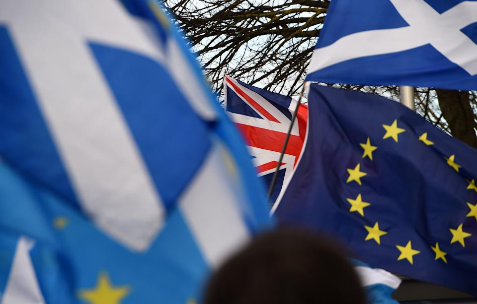 Pro-Union activists wave a Union flag (C) as Scottish Saltire and EU flags fly during an anti-Conservative government, pro-Scottish independence, and anti-Brexit demonstration outside Holyrood, the seat of the Scottish Parliament in Edinburgh on February 1, 2020. - Britain began its post-Brexit uncertain future outside the European Union on Saturday after the country greeted the historic end to almost half a century of EU membership with a mixture of joy and sadness. There were celebrations and tears on Friday as the EU's often reluctant member became the first to leave an organisation set up to forge unity among nations after the horrors of World War II. (Photo by ANDY BUCHANAN / AFP) (Photo by ANDY BUCHANAN/AFP via Getty Images)