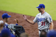 Los Angeles Dodgers starting pitcher Max Scherzer is greeted at the dugout after being pulled during the eighth inning of the team's baseball game against the San Diego Padres, Thursday, Aug. 26, 2021, in San Diego. (AP Photo/Gregory Bull)