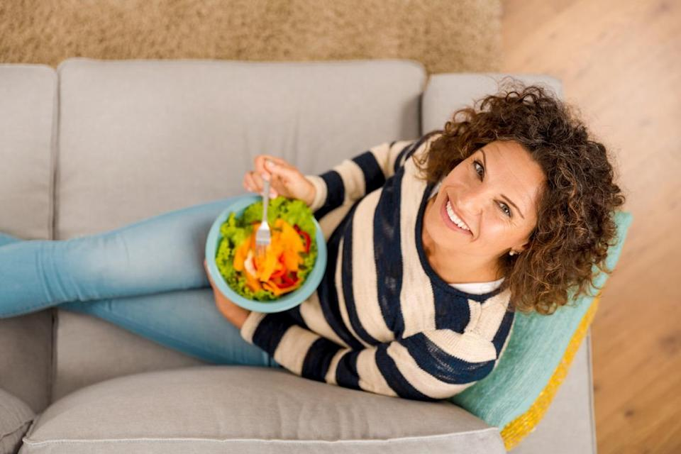 woman on the sofa eating a healthy salad