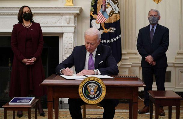 PHOTO: President Joe Biden signs executive orders as part of the COVID-19 response as Vice President Kamala Harris and Director of NIAID Anthony Fauci look on in the State Dining Room of the White House in Washington, D.C., Jan. 21, 2021. (Mandel Ngan/AFP via Getty Images, FILE)