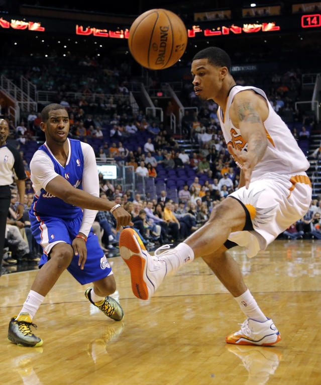 Los Angeles Clippers' Chris Paul, left, passes around Phoenix Suns' Gerald Green during the first half of an NBA basketball game, Tuesday, March 4, 2014, in Phoenix. (AP Photo/Matt York)