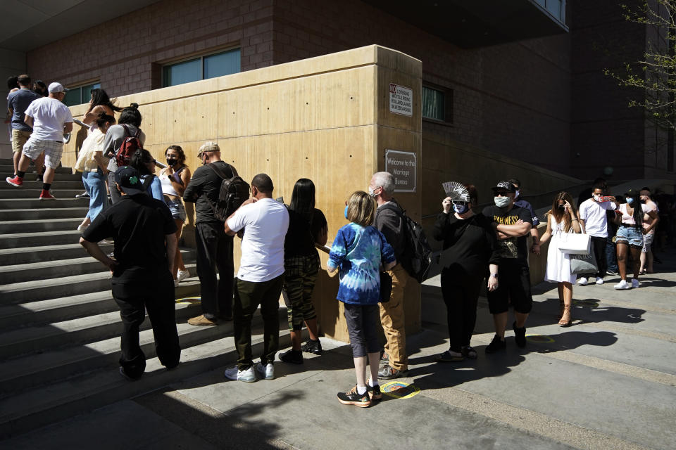 People wait in line for marriage licenses at the Marriage License Bureau, Friday, April 2, 2021, in Las Vegas. The bureau was seeing busier than normal traffic ahead of 4/3/21, a popular day to get married in Las Vegas. (AP Photo/John Locher)