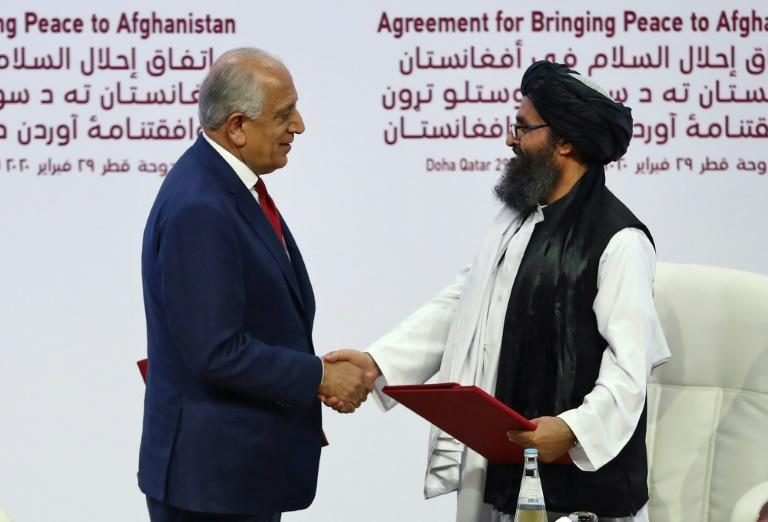 US Special Representative for Afghanistan Reconciliation Zalmay Khalilzad (left) and Taliban co-founder Mullah Abdul Ghani Baradar shake hands after signing a peace agreement in Doh in February 2020 (AFP Photo/KARIM JAAFAR)