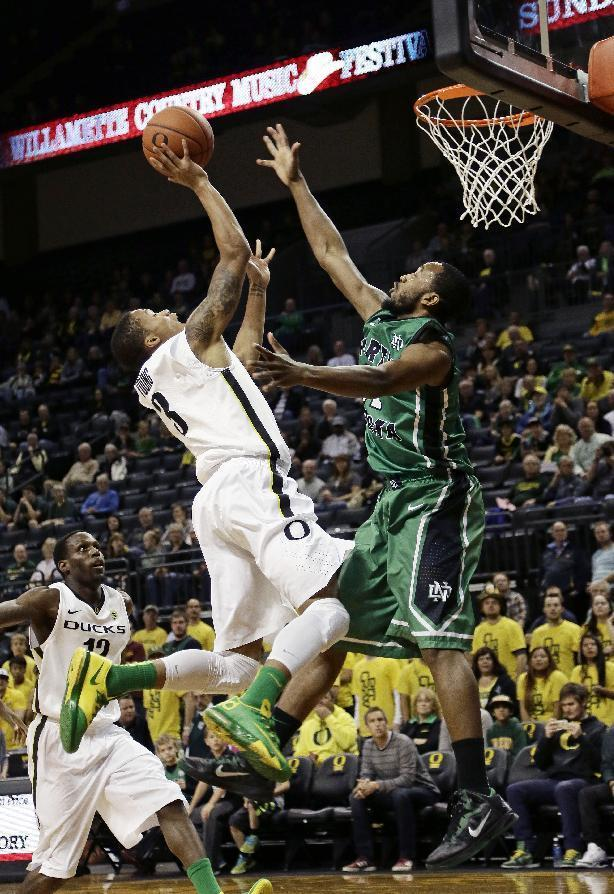 Oregon guard Joseph Young, top left, drives to the basket against North Dakota guard Jamal Webb during the first half of an NCAA college basketball game in Eugene, Ore., Saturday, Nov. 30, 2013. (AP Photo/Don Ryan)